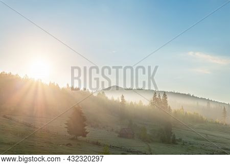 Scenic Beautiful Panoramic Landscape View Of Old Small Wooden Hut Cabin On Green Mountain Hill Fores