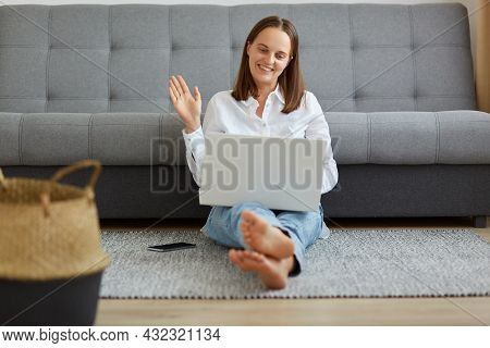 Portrait Of Young Beautiful Woman Using A Laptop Computer At Home While Sitting On The Floor Near So