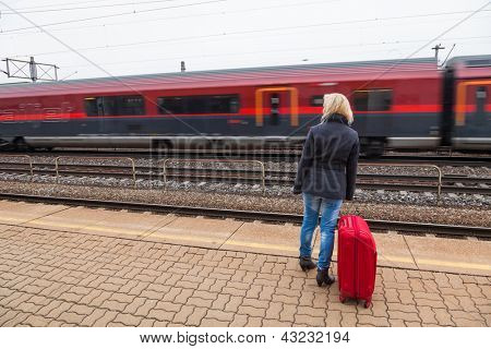 a young woman with luggage waiting on the platform of a railway station for their train. train delays