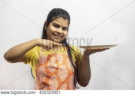 A Pretty Indian Housewife Woman Wearing Cooking Apron With A Serving Plate In Hand Pointing On White