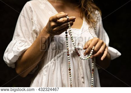 Japa Mala 108 Beads From Natural Stones. Woman's Hands Close Up. Pray And Meditation. Buddhist Jewel
