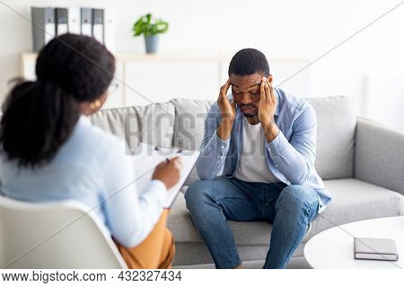 Depressed Black Man Rubbing His Temples, Consulting Psychologist, Sitting On Couch At Counselors Off