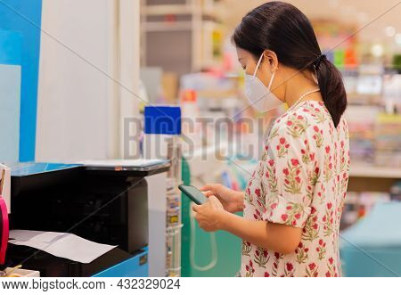 Cropped Image Of Female In Protective Mask  Holding Cell Phone With Printer To Print The Document