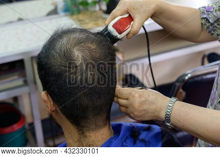 Close-up Of Hairdresser Using Electric Hair Clipper For Cut Human Head Hair In Barber Shop. Conceptu