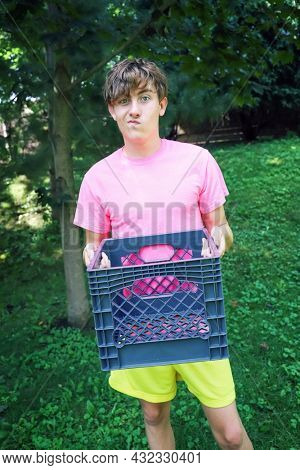 Teen boy making a funny face and holding a milk crate for the social media milk crate challenge