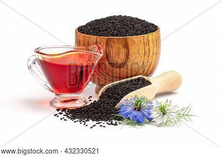 Black Cumin Oil In Gravy Boat And Nigella Sativa Flowers. Nigella Sativa Seeds In Wooden Scoop Isola