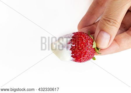Female Hand Holds A Strawberry Berry With Cream. Juicy, Sweet, Ripe, Red Strawberries On A White Bac