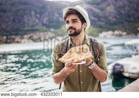 Young Man Eats A Piece Of Appetizing Pizza. Hungry Guy Holds A Piece Of Pizza In His Hands, Looks At