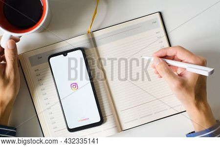 Logo Of Mobile Application Developed By Facebook Instagram On Smartphone Screen, Male Hands Making E