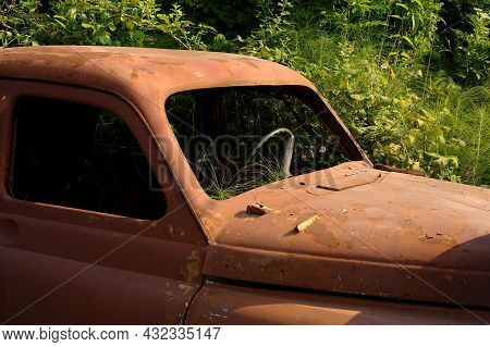 A Rusty Old Car Overgrown With Greenery. Abandoned City, Fleet.