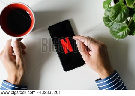Top View Of Male Hands Using Netflix Mobile App On Smartphone In Morning Over Cup Of Coffee Indoors.