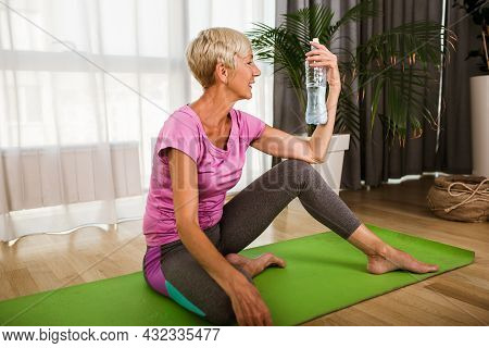 Mature Professional Woman Exercising And Stretching Her Body Doing Flexibility Exercises, She Drink