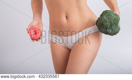A Faceless Woman In White Panties Holds A Donut And Broccoli On A White Background. Food Habits.