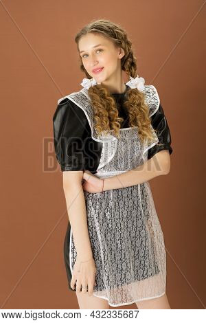Cheerful Blonde Teen Girl In Retro School Uniform. Portrait Of Graduate Girl With Two Curly Braids W
