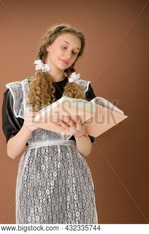 Teen Girl In Retro School Uniform Reading Book. Curious Graduate Teenage Girl With Braided Hair Wear
