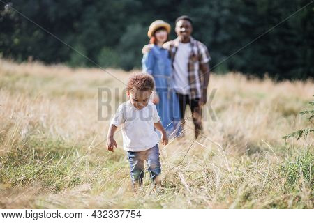 Pretty African Boy Running And Playing Among High Grass While His Multiracial Parents Standing In Hu