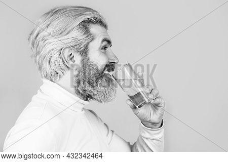 Smiling Male Holding Transparent Glass In Her Hand. Bearded Man Drinking Water. Male Drinking From A