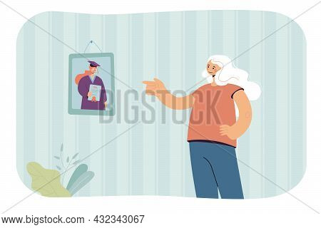 Elderly Woman Pointing At Graduation Photo On Wall. Senior Remembering Youth And Time At University