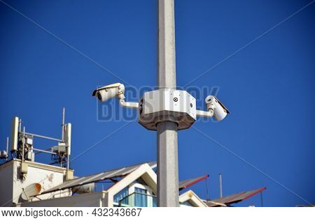 Street surveillance cameras hang on a pole against the background of the sky. A video monitoring camera on the city embankment. The concept of security resort. 30 July, 2021. Marmaris,Turkey