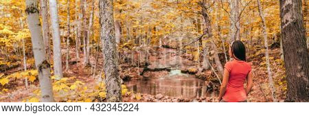 Fall forest woman hiking in autumn nature landscape panoramic. Girl enjoying outdoor environment looking at river and yellow foliage banner.