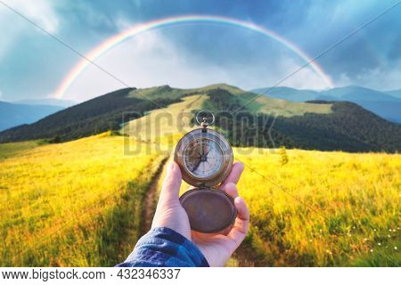 Man with old metal compass in hand on mountains road. Travel concept. Lush green grassy meadows and beautyful rainbow on background. Landscape photography