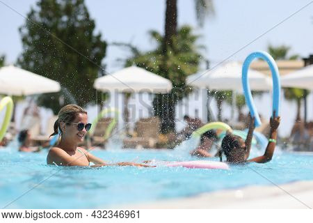 Young Woman Is Engaged In Aqua Aerobics In Outdoor Pool