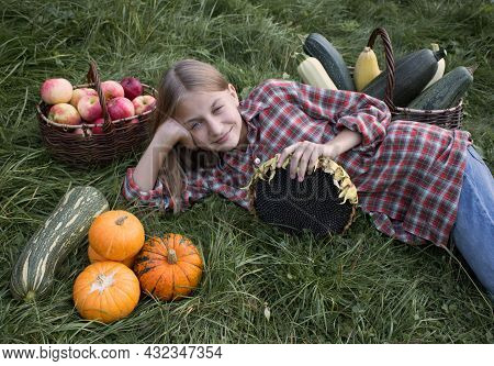 A Blonde Girl In A Plaid Shirt And Jeans Lies On The Green Grass Next To Vegetables And Fruits. She