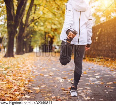 Fit Athletic Woman Doing Stretching Before Jogging In The Autumnal City Park. Young Fitness Female R