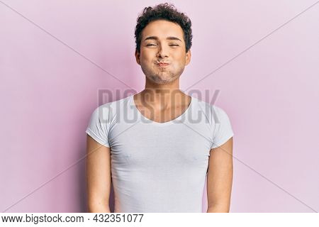 Young handsome man wearing casual white t shirt puffing cheeks with funny face. mouth inflated with air, crazy expression.