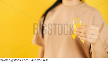 A Woman Holding A Yellow Gold Ribbon In Her Hand On A Yellow Background, Bone Cancer, Awareness Of C
