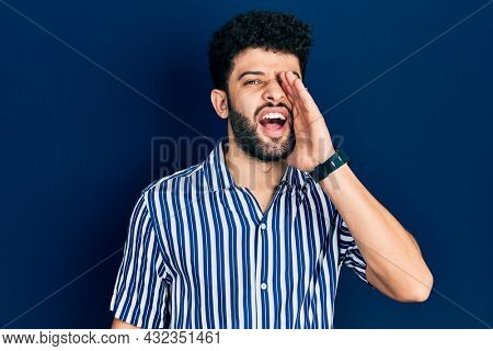 Young arab man with beard wearing casual striped shirt shouting and screaming loud to side with hand on mouth. communication concept.