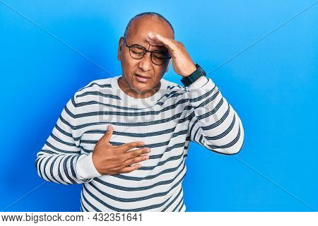 Middle age latin man wearing casual clothes and glasses touching forehead for illness and fever, flu and cold, virus sick