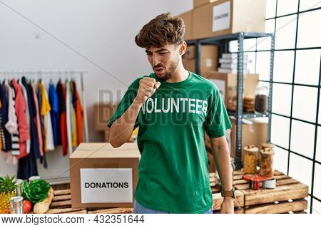 Young arab man wearing volunteer t shirt at donations stand feeling unwell and coughing as symptom for cold or bronchitis. health care concept.