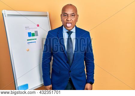 Middle age latin man wearing business clothes on chart presentation sticking tongue out happy with funny expression. emotion concept.