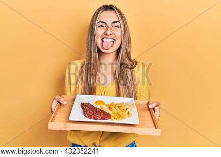 Beautiful hispanic woman holding tray with meat loaf and fried egg sticking tongue out happy with funny expression.