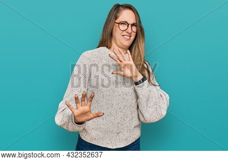 Young blonde woman wearing casual sweater and glasses disgusted expression, displeased and fearful doing disgust face because aversion reaction. with hands raised