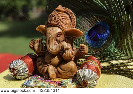 Beautiful Lord Ganesha Idol Worshiped During Ganesh Chaturthi Festival With Peacock Feather In Backg