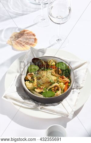Elegant seafood stew with cod fish and vegetables in pot. Healthy fish dish - baked codfish, shrimp, mussels on broccoli and tomato. Serving white tablecloth and glass in summer day with shadow