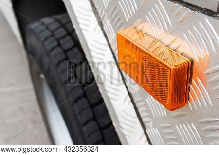 Turn Signal On The Truck. Fragment Of A Truck With An Orange Turning Signal On The Background Of The