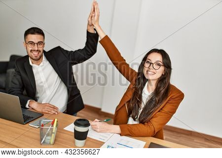 Two business executives raised up hands hitting five at the office.