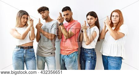 Group of young friends standing together over isolated background holding symbolic gun with hand gesture, playing killing shooting weapons, angry face