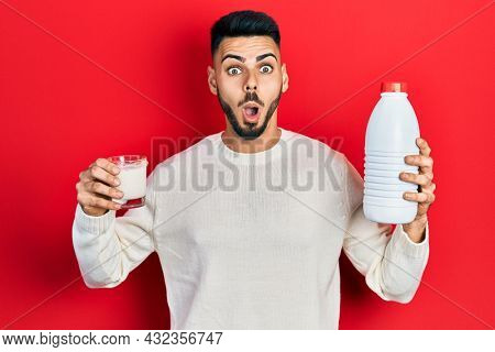 Young hispanic man with beard holding glass of milk and plastic bottle afraid and shocked with surprise and amazed expression, fear and excited face.