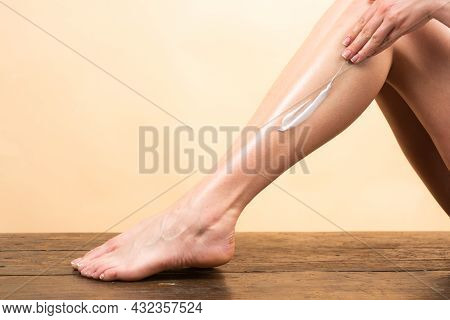Cosmetic Cream On Woman Leg With Clean Soft Skin. Applying Moisturizer Cream On Legs. Cellulite Or A
