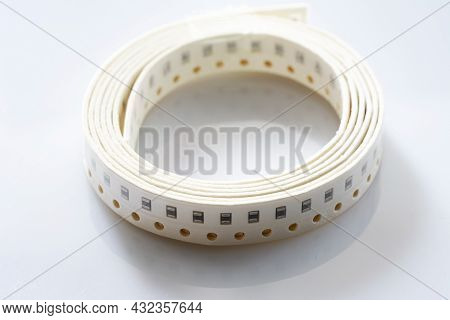 Electronic Component On White Background. Smd Components In Black Plastic Carrier Tape With Copyspac