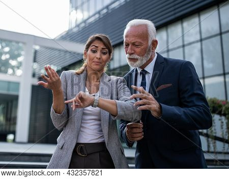 Senior Businessman And Young Businesswoman Looking At Wristwatch And Waiting For Somone In Front Of