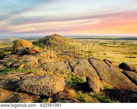 Morning scene with old stones in steppe. Take it in Ukraine
