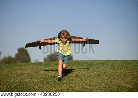 Child Boy Like A Pilot With Toy Wings Against Blue Sky. Kids Freedom Concept. Dreams Of Becoming A P