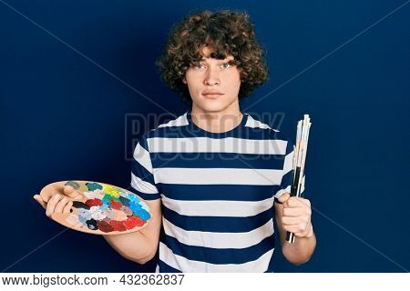 Handsome young man holding paintbrush and palette skeptic and nervous, frowning upset because of problem. negative person.