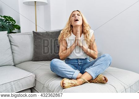 Beautiful blonde woman sitting on the sofa at home begging and praying with hands together with hope expression on face very emotional and worried. begging.
