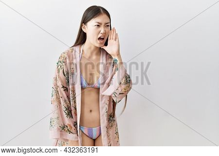 Young asian woman wearing bikini an floral kimono shouting and screaming loud to side with hand on mouth. communication concept.
